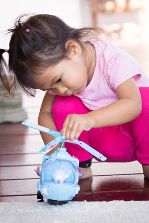 intend: Cute little girl is playing toy
