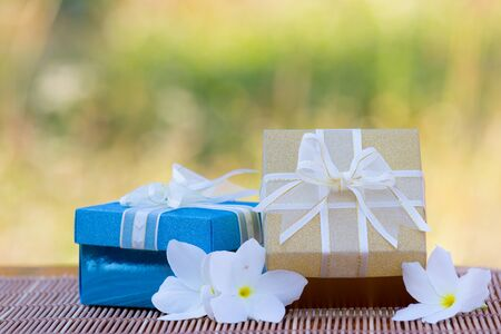 Colorful gift boxes  on wooden mat on meadow background photo