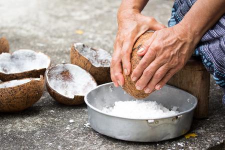 Oude vrouw zitten op kokos rasp en rasp kokosnoot in de kom