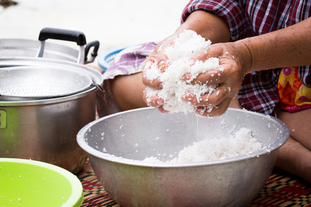 Woman is squeezing coconut meat to get the coconut milk for cooking Standard-Bild