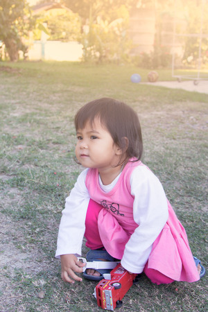Cute little girl is playing with her toy in the garden in soft style photo