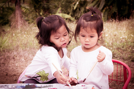 Cute little girls are painting with watercolor together in vintage style photo