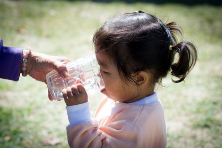 vaso de agua: Ni�a linda que el agua potable de vidrio Foto de archivo