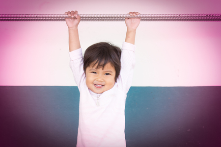 Cute little girl holding on the bar photo