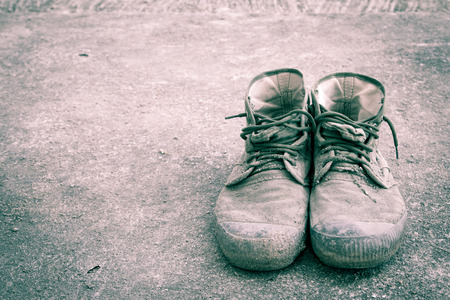 Old shoes on floor in vintage style photo