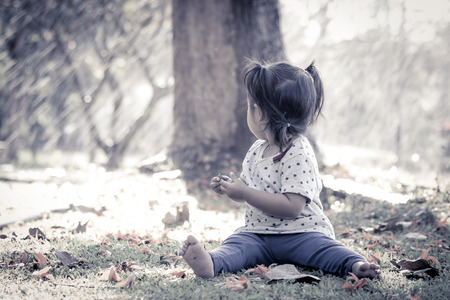 Cute little girl is playing in the park in vintage style photo