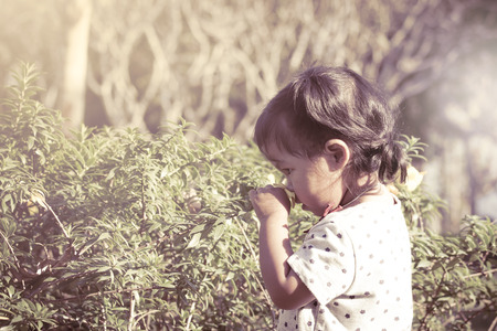Cute little girl is smelling flower in the park in vintage style photo