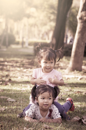 Cute little girls are playing together in the park in vintage style photo