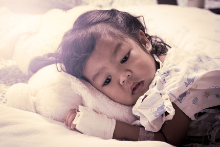bebe enfermo: Niña enferma se acostó en la cama en el hospital