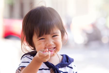 asian child: Cute little girl is eating icecream