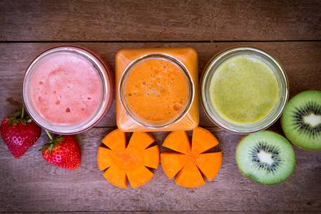 zumo verde: Vista superior de fresa, kiwi y jugo de zanahoria mezclado en el fondo de madera Foto de archivo