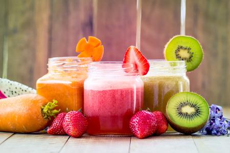 jugo de frutas: El color dulce de jugo de fruta mezcla mezclado en el fondo de madera