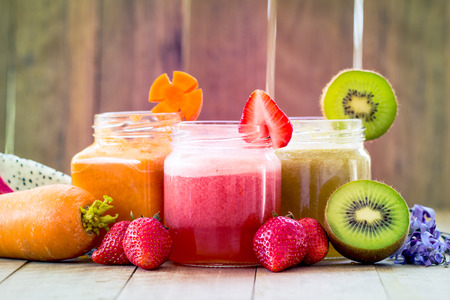 orange juice glass: Sweet color of mix fruit juice blended on wooden background Stock Photo