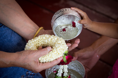 natual: Pour water on the hands of revered elders and ask for blessing in Songkran festival Stock Photo