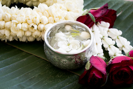 water with jasmine flower in silver bowl and jasmine garland on banana leaf background Reklamní fotografie