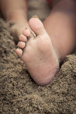 Little girl feet in sand photo