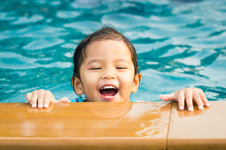 Cute little girl having fun in the swimming pool