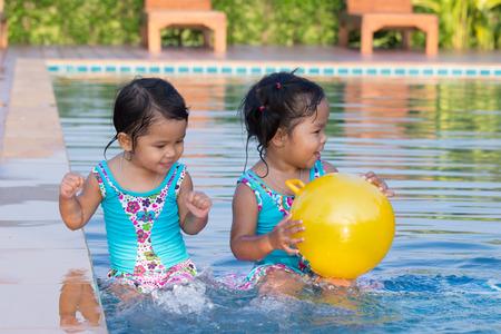 cute little girls: Ni�as lindas que se divierten en la piscina Foto de archivo