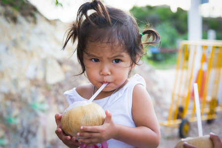 little girl drinking coconut juice in summer time