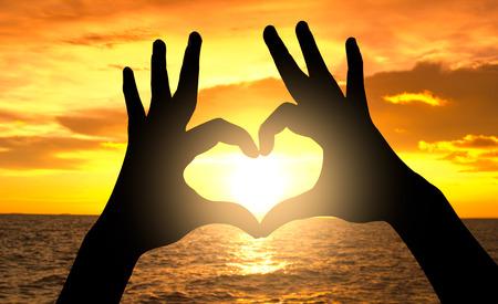Silueta de mano en forma de corazón en la puesta de sol sobre el mar Foto de archivo - 40921337
