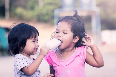 niños comiendo: dos niñas se divierten comer helado juntos, filtro de color de la vendimia Foto de archivo