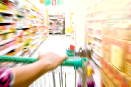blurred image of woman hand hold shopping cart in supermarket photo