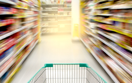 food store: blurred image of shopping in supermarket with shopping cart Stock Photo