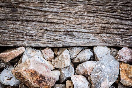 sleeper: old wooden sleeper with rock on railway track Stock Photo