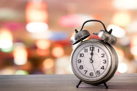 male wood tick: retro alarm clock on table on bokeh background Stock Photo