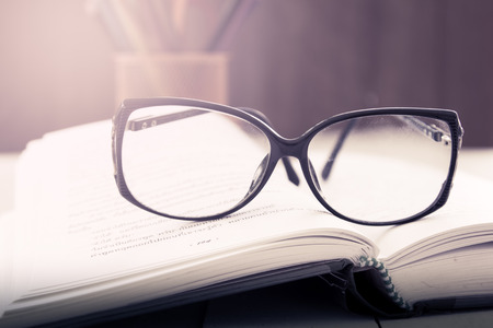 color in: glasses on open book on wooden table in vintage color filter