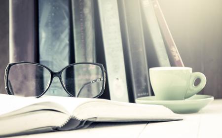bril op open boek met een kopje koffie op houten tafel in vintage kleurfilter Stockfoto