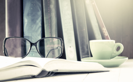 glasses on open book with cup of coffee on wooden table in vintage color filter