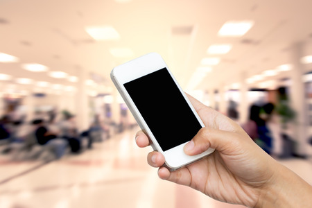 gente aeropuerto: mano de la mujer mantenga teléfono inteligente, tableta, teléfono celular en borrosa de estilo de vida en la zona de espera silla en fondo aeropuerto Foto de archivo