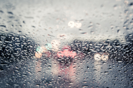 blurred image of traffic view through a car windscreen covered in rain,vintage filter Reklamní fotografie