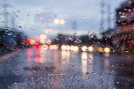 wazig beeld van het verkeer zicht door de voorruit bedekt met regen