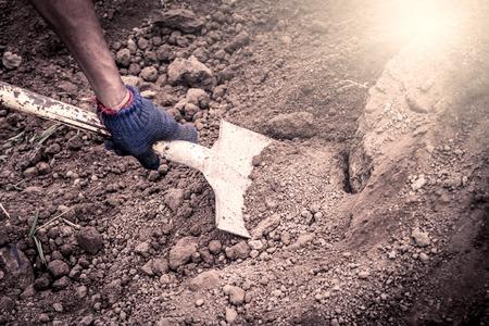 work gloves: man hand shoveling the soil on garden,vintage filter