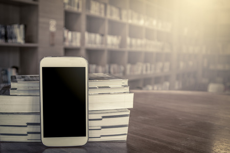 antique books: smart phone,cellphone with stack of book on blur bookshelf background in vintage color tone