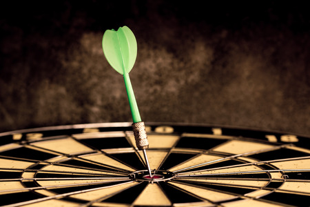 Success hitting target aim goal achievement. Dart in target center on dartboard, vintage effect filter Stockfoto