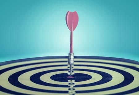 metas: Éxito golpear logro de la meta objetivo de destino. Dardo en el centro de destino en el tablero de dardos, filtro de efecto vintage