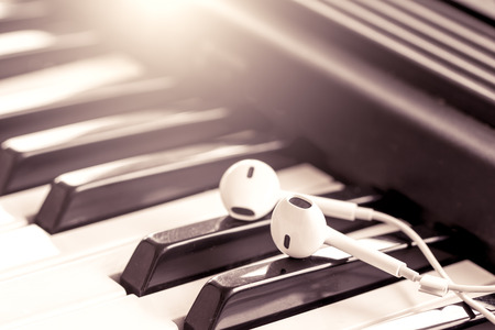 earphone  on piano key in vintage color tone,music concept