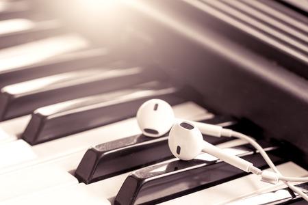 fortepian: słuchawki na klucz fortepianu w odcieniu rocznika, pojęcie muzyki Zdjęcie Seryjne