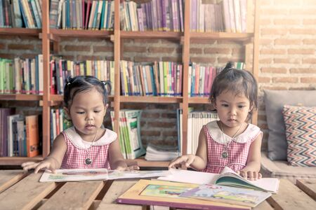 intelligently: two little girls reading books together in library,vintage filter Stock Photo