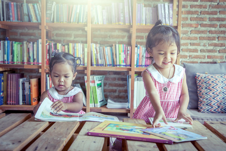 two little girls reading books together in library,vintage filter Reklamní fotografie