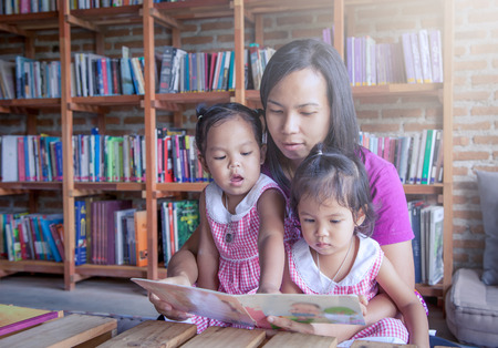 intelligently: Mother and little daughter reading book together in library,soft color filter Stock Photo