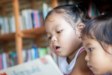 intelligently: cute little girl reading book in library