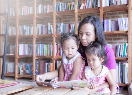 brotherhood: Mother and little daughter reading book together in library,soft color filter Stock Photo