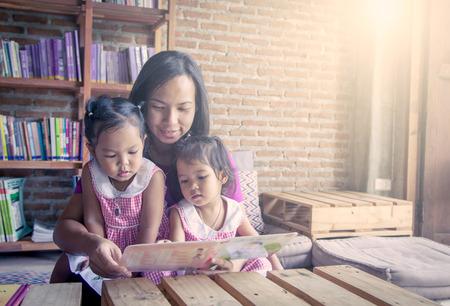 gemelas: Madre y pequeño libro de lectura de la hija junto en biblioteca, filtro de color suave