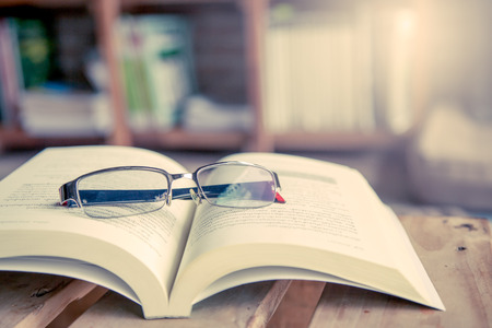 glasses on open book on wooden table in library in vintage color tone