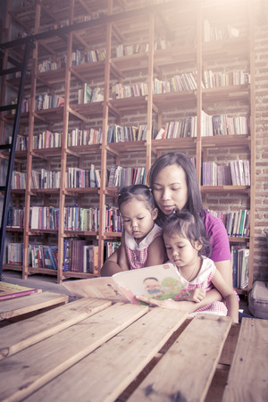 intelligently: Mother and little daughter reading book together in library,vintage color filter Stock Photo
