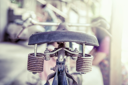 metal spring: Closeup old bike saddle with rusty metal spring in vintage color tone Stock Photo